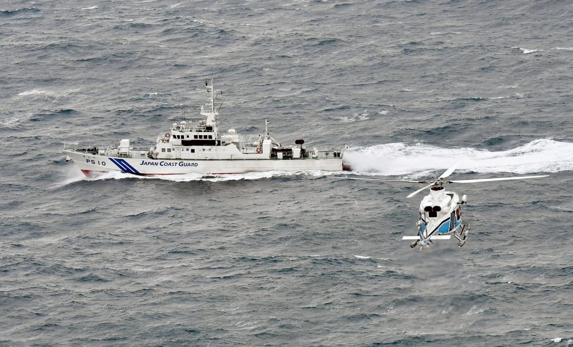 A Japan Coast Guard patrol boat and a helicopter search for the capsized Daifuku Maru and its crew off the coast of Matsue, Shimane Prefecture, on Wednesday. | KYODO