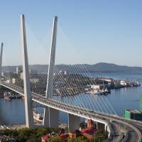Vehicles pass over Golden Bridge in Vladivostok, in Russia's Far East, in September last year. Sources say Japan and Russia have decided to create a ¥100 billion fund to be used for development projects in Russia, including in the Far East port city. | BLOOMBERG