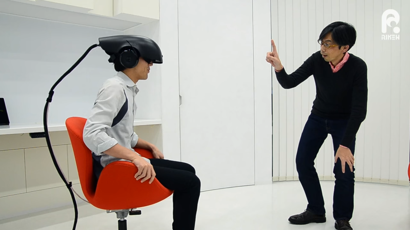 Riken researcher Naotaka Fujii (right) tests a 'substitutional reality' system that lets people experience how a prerecorded 360-degree video can be mixed into real-life surroundings.   COURTESY OF RIKEN