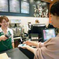 A woman displays a digital voucher on her smartphone at a Starbucks outlet in Shinagawa Ward, Tokyo, in 2014. | KYODO