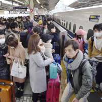 Passengers departing for the year-end holidays pack a bullet train platform at Tokyo Station Thursday morning as the annual exodus peaked. | KYODO