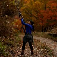 Hunter Masami Hata shoots at a duck in a forest outside Hakusan, Ishikawa Prefecture, on Nov. 20. | REUTERS