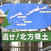 A man walks in front of a sign calling for the return of four Russian-held islands to Japan, in Nemuro, Hokkaido, on Wednesday.   KYODO