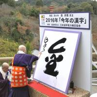 The kanji for kin, meaning gold or money, is written at Kiyomizu Temple in Kyoto on Monday by chief priest Seihan Mori after it was selected the kanji of the year. | KYODO