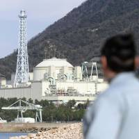 A resident watches the Monju fast-breeder reactor in Tsuruga, Fukui Prefecture, on Wednesday. | KYODO