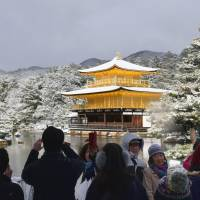 Tourists admire snow-covered Kinkakuji Temple in Kyoto on Jan. 20. | KYODO