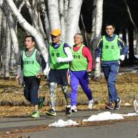 Blind marathon participants jog with escort runners at a park in Sapporo in November. | KYODO