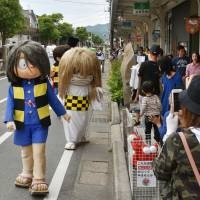 Characters based on spirits and monsters participate in a parade on Mizuki Shigeru Road in Sakaiminato, Tottori Prefecture, on June 4. | KYODO