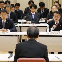 Industry minister Hiroshige Seko (right) speaks to Fukui Gov. Issei Nishikawa (foreground) about the fate of the Monju fast-breeder reactor on Wednesday in Tokyo. | KYODO