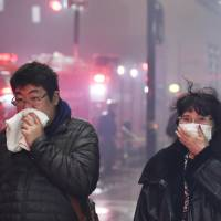 Residents of Itoigawa, Niigata Prefecture, cover their noses and mouths as a fire charged through the city on Thursday. | KYODO