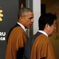 Prime Minister Shinzo Abe and U.S. President Barack Obama and talk after taking part in a photo session at the Asia-Pacific Economic Cooperation summit in Lima, Peru, on Nov. 20. | REUTERS