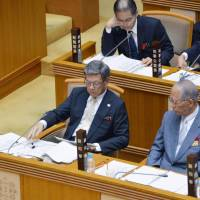 Okinawa Gov. Takeshi Onaga (left) receives a memo during a prefectural assembly session on Monday. The memo shows the date and time in which the Supreme Court will issue its ruling on the government's move to relocate the Futenma air base in Okinawa. | KYODO