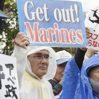 Protesters hold signs Thursday near a site where the government hosted a ceremony to mark the land return by the U.S. in the city of Nago in Okinawa. | KYODO