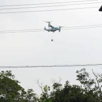 A U.S. Marine Corps MV-22 Osprey carrying an object is seen flying over the village of Ginoza in Okinawa Prefecture on Tuesday. | GINOZA MUNICIPAL GOVERNMENT/ VIA KYODO