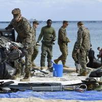 U.S. military personnel Saturday collect wreckage from the debris field left by a U.S. Marine Corps MV-22 Osprey aircraft that crash-landed Tuesday off the coast of Okinawa Prefecture.   KYODO