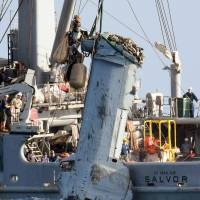 The U.S. military on Dec. 21 recovers debris, believed to be a main wing section from an MV-22 Osprey tilt-rotor aircraft that ditched off Nago, Okinawa Prefecture, earlier in the month. | KYODO