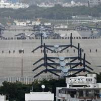 U.S. personnel line up near MV-22 Osprey tilt-rotor aircraft at Marine Corps Air Station Futenma in Okinawa Prefecture on Monday. | KYODO