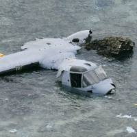 A severely damaged MV-22 Osprey aircraft lies on a reef near the coast of Nago, Okinawa Prefecture, on Wednesday. | KYODO