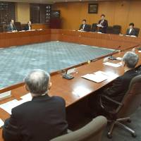 A health ministry panel announces measures to prevent death by overwork and changes to overtime regulations during a meeting in Tokyo on Monday. | KYODO