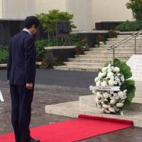 Prime Minister Shinzo Abe lays a wreath at the National Memorial Cemetery of the Pacific in Honolulu on Monday morning.   ERIC JOHNSTON