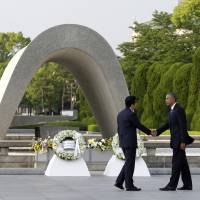 U.S. President Barack Obama shakes hands with Prime Minister Shinzo Abe at Hiroshima Peace Memorial Park in Hiroshima, on May 27, as Obama became the first sitting U.S. president to visit the site of the world's first atomic bomb attack. Abe said Monday he will visit Pearl Harbor with Obama at the end of this month, becoming the first leader of his country to go to the U.S. Naval base in Hawaii that Japan attacked in 1941. | AP