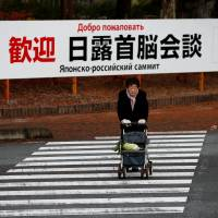 A woman walks in front of a sign board on Thursday that reads 'Welcome to the Japan-Russia summit meeting' near the summit's venue in Nagato, Yamaguchi Prefecture. | REUTERS