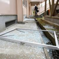 Broken window glass lies scattered outside a junior high school gymnasium in Takahagi, Ibaraki Prefecture, on Thursday after a magnitude-6.3 earthquake. | KYODO