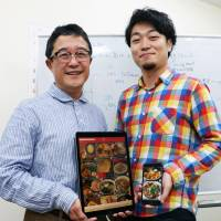 Toru Domon (left) and Yuta Hirobe display an app for smartphones and tablets, Mainichi ga Ramen, which allows noodle lovers to find the most popular bowls across Japan, on Nov. 1 in Sapporo. | KYODO