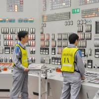 Workers in the control room restart reactor 1 at Kyushu Electric Power Co.'s Sendai nuclear plant in Kagoshima Prefecture Thursday night. | KYODO