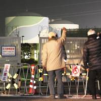 Men raise their fists in protest Thursday in front of the No. 1 reactor at the Sendai nuclear power plant in Kagoshima Prefecture, which was restarted the same day.   KYODO