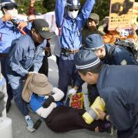Police officers try to remove a protester opposed to the construction of a helipad in the U.S. military's Northern Training Area in the village of Higashi, Okinawa Prefecture, on Wednesday. | KYODO