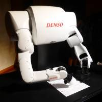 A robot developed by auto parts maker Denso Corp. writes Torobo-kun's answers on paper during a demonstration on Nov. 14 in Chiyoda Ward, Tokyo. | SHUSUKE MURAI