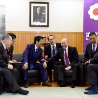 Russian President Vladimir Putin (third from right) speaks with Prime Minister Shinzo Abe (third from left), during a visit to the Kodokan Judo Institute in Tokyo on Dec. 16. | BLOOMBERG