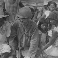 William Schull (center), a military medic during World War II, crosses the Cagayan River on the Philippine main island of Luzon in this photo taken around July 1945. | COURTESY OF WILLIAM SCHULL / VIA KYODO