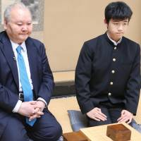 Professional shogi player Sota Fujii (right), 14, poses after defeating Hifumi Kato, 76, in his debut match Saturday in Tokyo's Shibuya Ward. Fujii is the youngest pro in the game. | KYODO