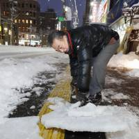 A man is seen shoveling snow on a street on Saturday evening in Sapporo. | KYODO