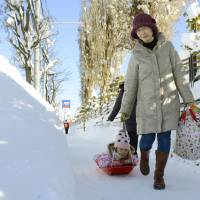 A young girl smiles as she is pulled on a sledge along a snow-covered sidewalk in Higashi Ward, Sapporo, on Saturday afternoon. | KYODO