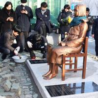 A statue symbolizing Korean 'comfort women' sits in front of the Japanese Consulate in Busan on Friday. | KYODO