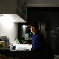 Hiroki Yamakawa, a freshman at Waseda University, poses for a photograph in his room at a dormitory in Tokyo on Nov. 11. Yamakawa's studies would likely not be possible without a ¥400,000 annual scholarship. | BLOOMBERG