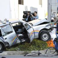A taxi that crashed through an intersection and onto a sidewalk in Tokyo's Kita-Aoyama district on Tuesday was seriously damaged. The accident injured six people, including the driver. | KYODO
