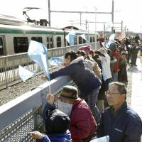 Local people attend the reopening ceremony for the new station in Shinchi, Fukushima Prefecture, on Saturday. The station on the Joban Line is on a section of line hardest hit by the 2011 Great East Japan Earthquake. | KYODO