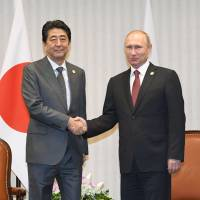 Prime Minister Shinzo Abe and Russian President Vladimir Putin shake hands ahead of their meeting on Nov. 19 on the sidelines of a Pacific Rim summit in Lima. | KYODO