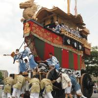People pull a huge decorated float on July 24 during the Yamahoko parade, part of Kyoto's traditional Gion Festival that was listed on UNESCO's Intangible Cultural Heritage list on Wednesday. | KYODO