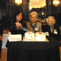 Yoko Tsuruoka (second from left), the wife of the current Japanese ambassador to Britain, cuts a cake to celebrate the 60th anniversary of the Japanese Women's Association in Great Britain with Meri Arichi (left), the association's chairwoman, on Oct. 11. | SETSUKO KATO / VIA KYODO