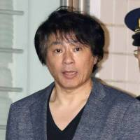 Pop star Aska is taken away by police, but later released. | KYODO