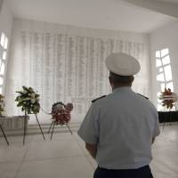 A naval officer pays his respects at the USS Arizona Memorial for those who died during the bombing of Pearl Harbor on the 75th anniversary of the attack. | AP