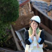 A woman stands in shock in front of her wrecked home in Mashiki, Kumamoto Prefecture. A second earthquake that struck early Saturday morning has caused extensive structural damage to buildings and roads. | KYODO