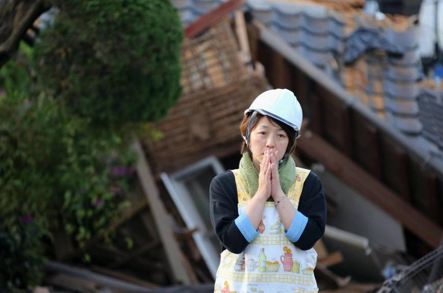 A woman stands in shock in front of her wrecked home in Mashiki, Kumamoto Prefecture. A second earthquake that struck early Saturday morning has caused extensive structural damage to buildings and roads.