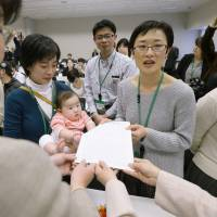 Mothers deliver a petition to lawmakers in Tokyo on March 23 demanding better access to day care. | KYODO