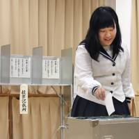 After the voting age was lowered, a third-year high school student casts her vote during a mayoral election in Ukiha, Fukuoka Prefecture, on July 3. | KYODO
